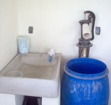 Our second floor laundry area, complete with hand pump connected to the ajibe (dry well).