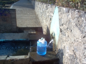 Filling our drinking water container from the natural springs in a nearby community.