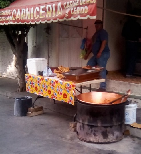 Carnitas are cooked in that bronze pot set inside the cut-off metal barrel.